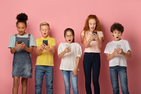 Kids of varying ages on their smartphones.