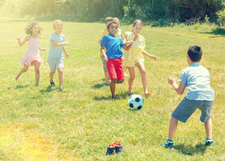 Children playing soccer outside.