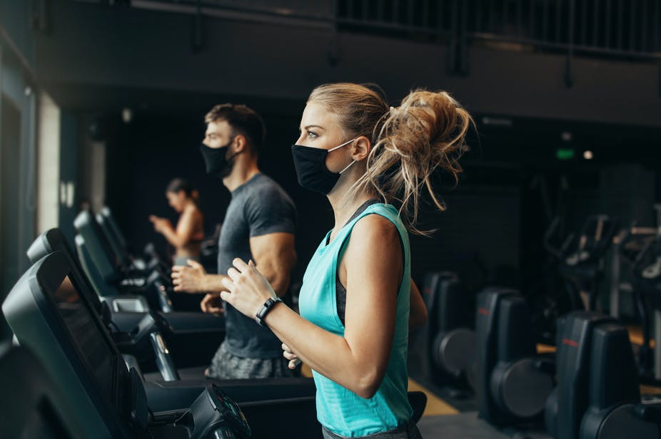 A man and a woman run on treadmills in the gym while wearing masks.