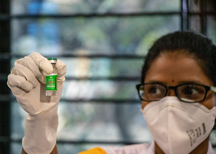 A healthworker wearing a mask holds up a vial of vaccine.