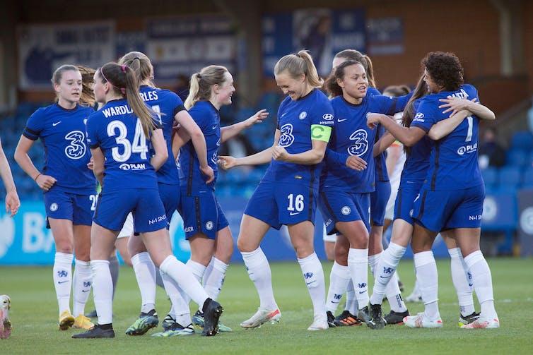 Women footballers congratulate each other.