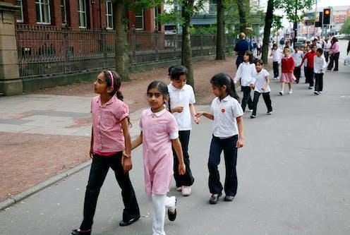 School children in uniform walk down a street in Manchester