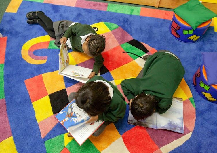 Primary school children sit on an Elmer the Elephant carpet reading