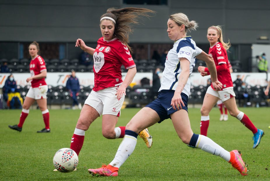 Women footballers chase after ball.