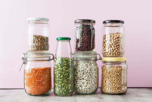 Assorted legumes stored in jam and mason jars.