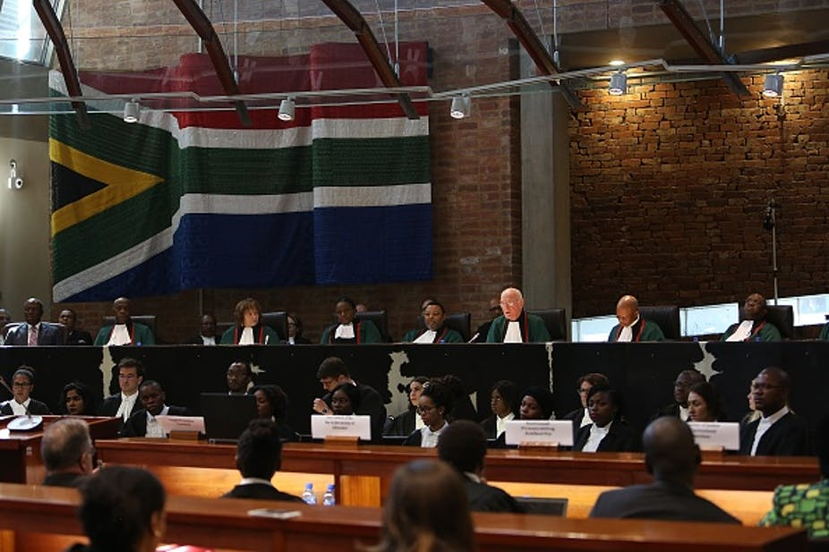 Judges and clerks with flag on the wall behind their seats