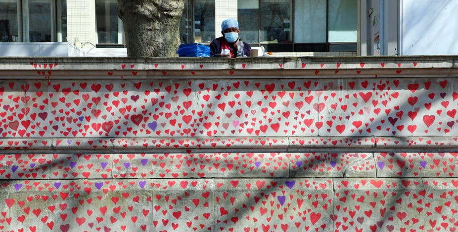 A hospital worker in PPE looks out over Hearts of the National Covid Memorial drawn by the Bereaved Friends and Family of Covid-19 on the embankment of the River Thames opposite the Houses of Parliament.