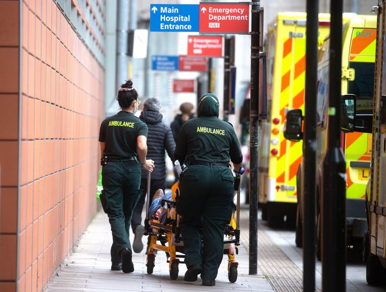 Two ambulance workers wheel a patient into hospital.