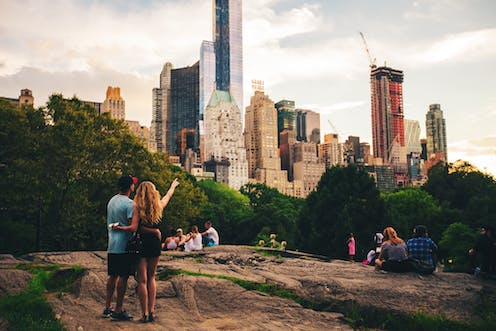 People in Central Park point towards the skyscrapers beyond the trees