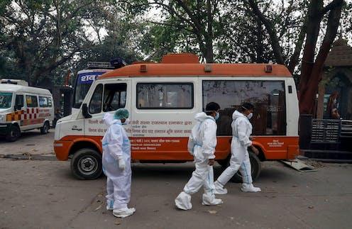 Relatives of COVID-19 victims walk past a van at Nigambodh Ghat crematorium in New Delhi