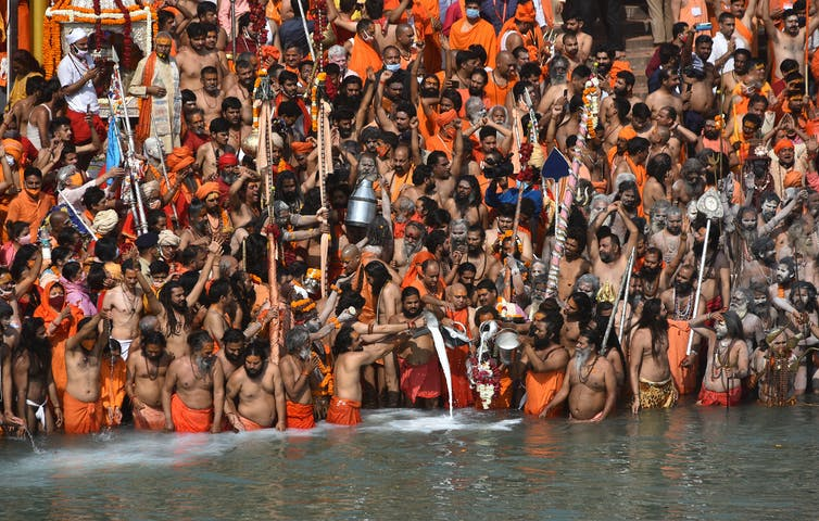 Indian holy men and other pilgrims take the holy dip in the Ganges River during the Kumbh Mela at Haridwar, Uttarakhand, India, April 14 2021.