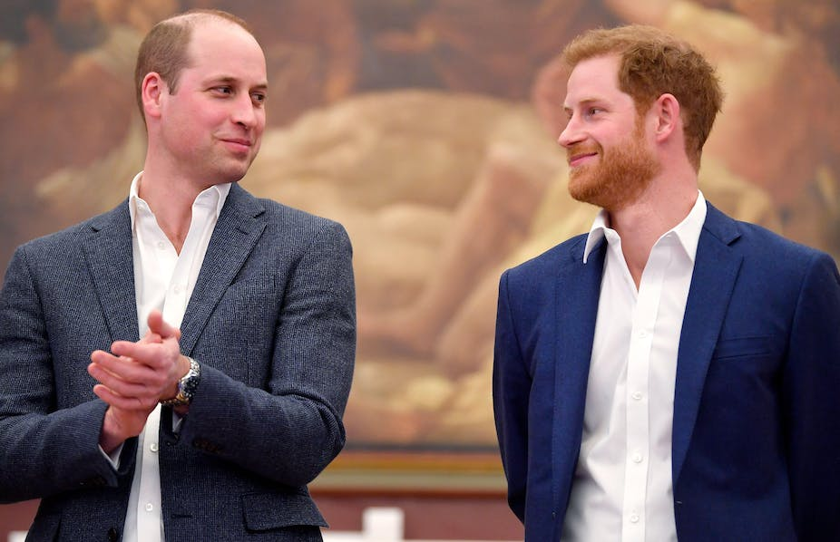 Prince William and Prince Harry looking at each other and smiling.
