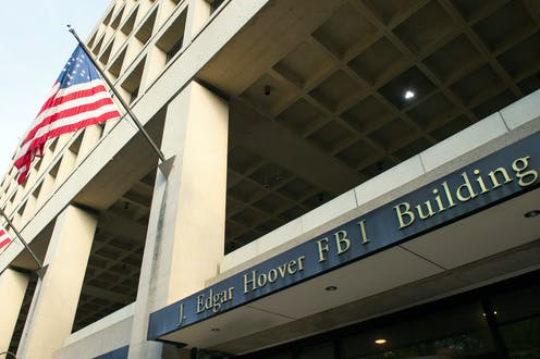 Close-up of the entrance to the FBI's J. Edgar Hoover headquarter building in Washington, DC with the building's name plaque and a flag