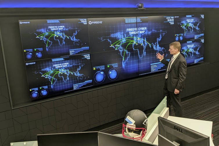 A man stands in front of a wall covered with computer displays showing maps of the world