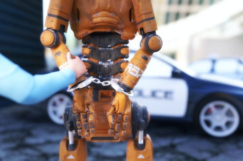 A humanoid robot stands with its arms in handcuffs behind its back, a blue-sleeved human arm holds one of the robot's arms, a police car in the background