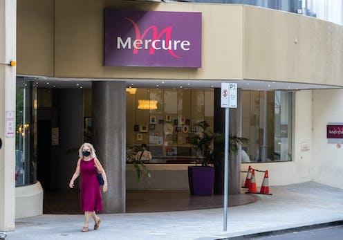 Woman wearing mask walks past Perth's Mercure hotel