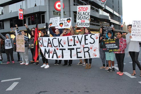 A group of people stand on a main road with banners that read 'Black lives matter' 'stop black deaths in custody and 'justice for fella''