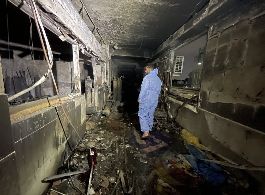 A man walks through a burned out hospital in Iraq.