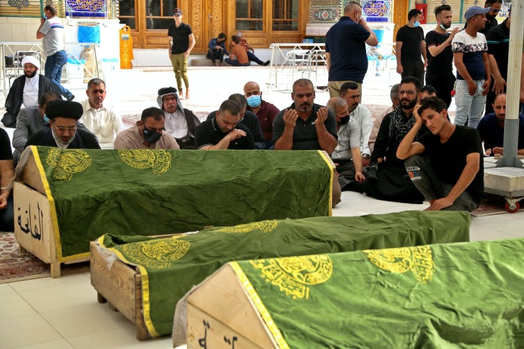 Mourners pray near the coffins of coronavirus patients who were killed in the hospital fire.