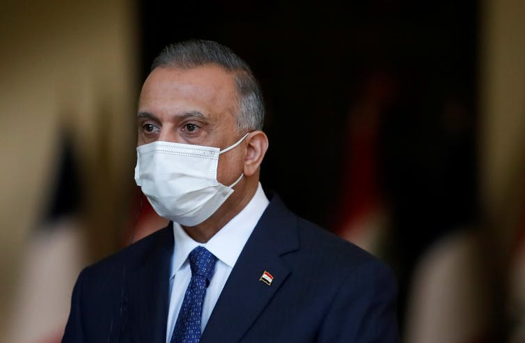 Iraqi Prime Minister Mustafa al-Kadhemi is seen wearing a face mask.