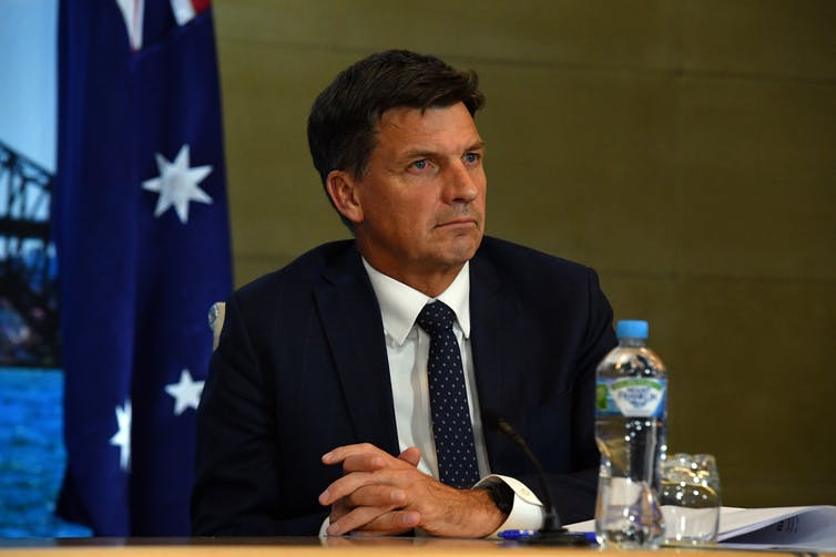 Angus Taylor sitting in front of an Australian flag, with a water bottle