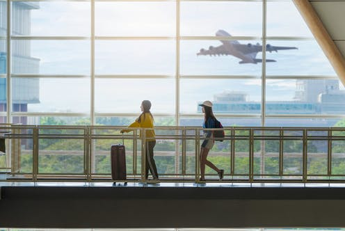 Two students walk through an airport terminal with a plane taking off outside