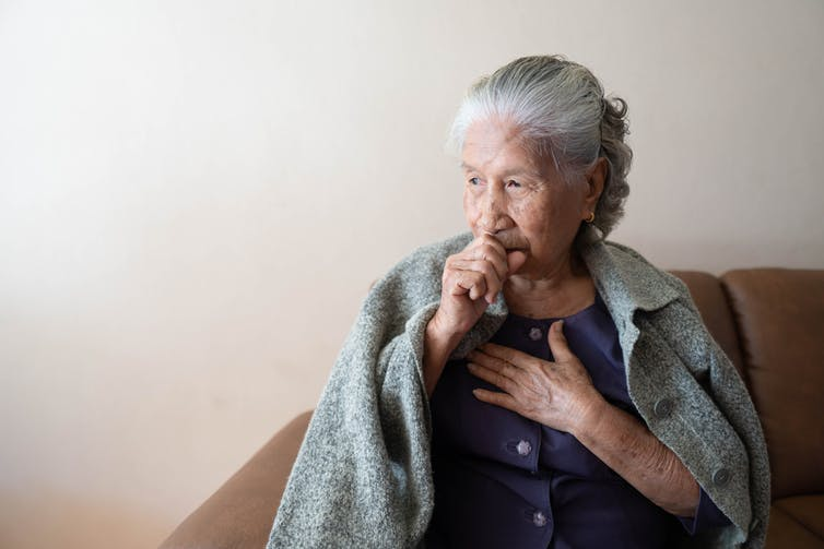 Elderly woman coughing with blanket over her