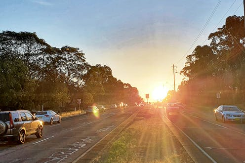 Cars driving at sunset along a divided multi-lane suburban road