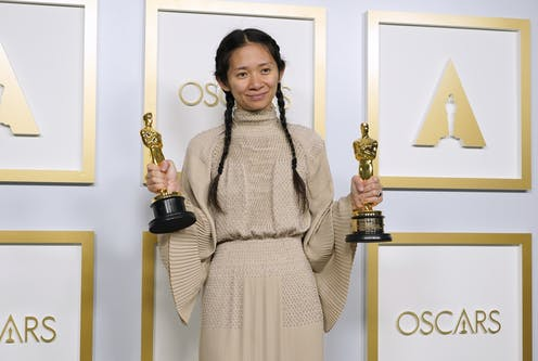 Chloe Zhao posing with her Oscar awards on a red carpet
