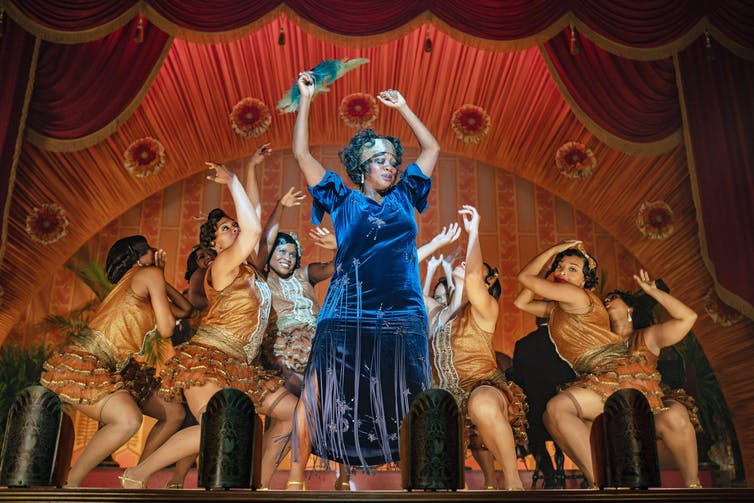 Black woman in blue dress dances on stage with backup dancers