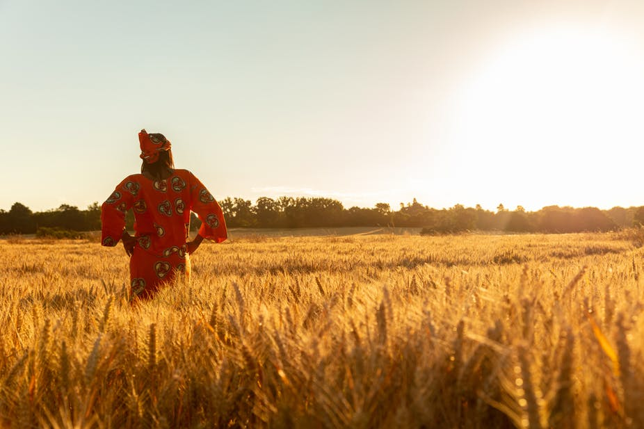 A woman stands in a field of crops