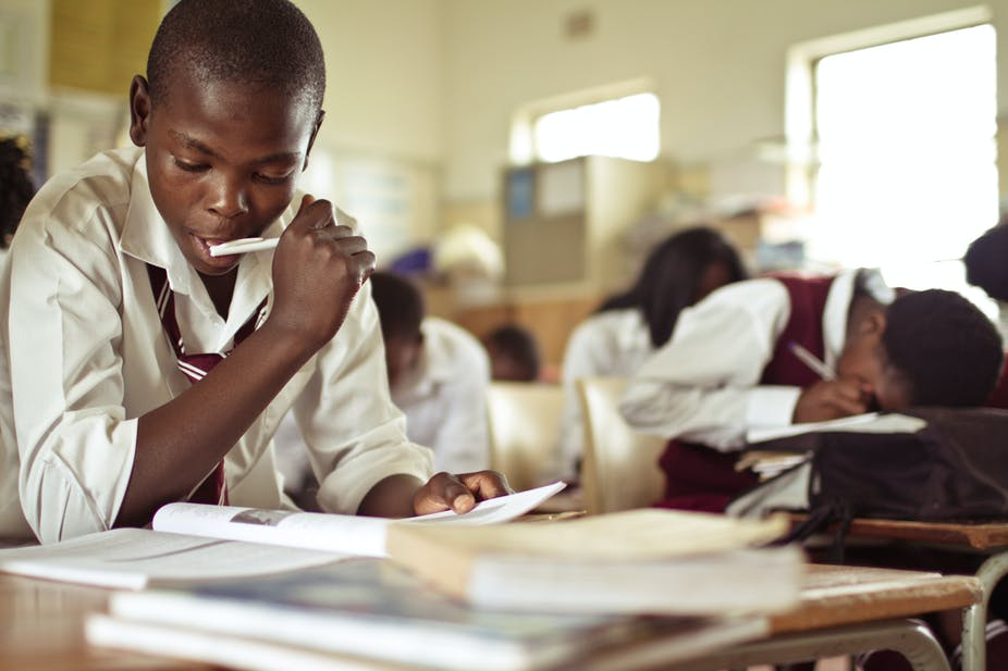 Closeup image of a young boy studying in a classroom.