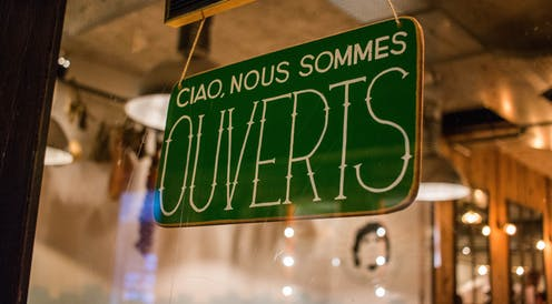 A store sign in French that reads 'Hello, we are open'