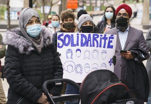 femmes et hommes manifestant, avec une banderole