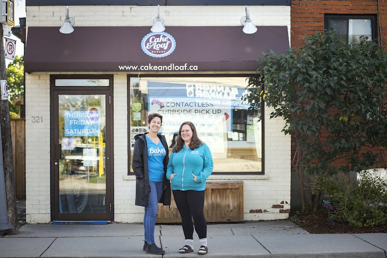 Two women stand in front of a bakery.
