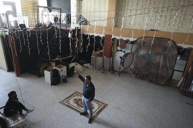 A man stands in an empty ballroom.