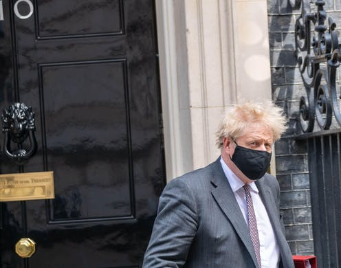 Boris Johnson leaving Downing Street wearing a face mask.