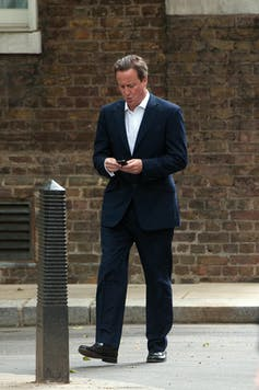 David Cameron walking down the street looking at his phone, appearing to text.
