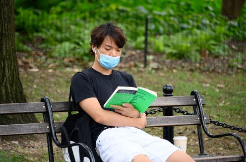 Person wearing face mask reads on park bench