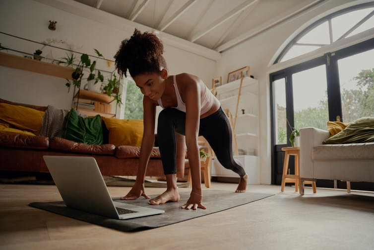 Young woman exercises to a video on her laptop.
