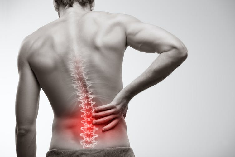 A man with a back rests his hand on the lumbar region.
