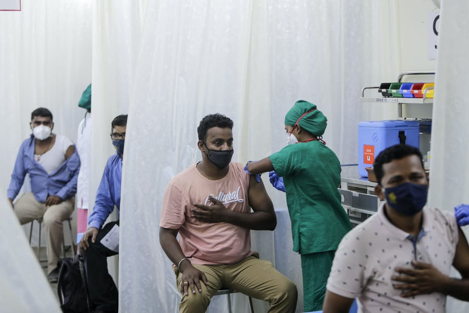 Men in a tent being vaccinated.