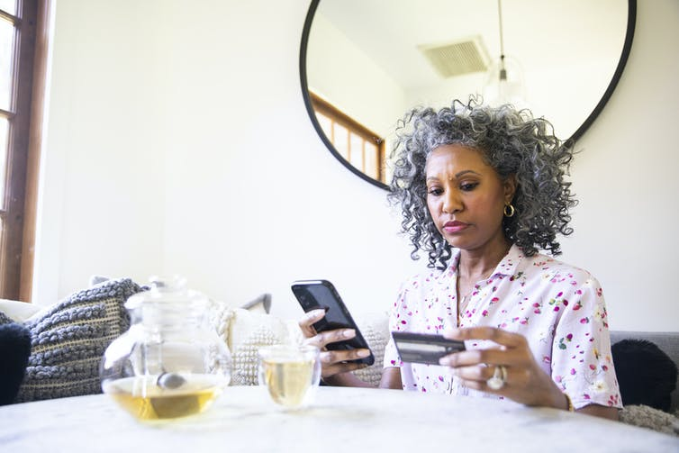 A middle-aged woman buying something with her credit card and mobile phone, sitting at a table.