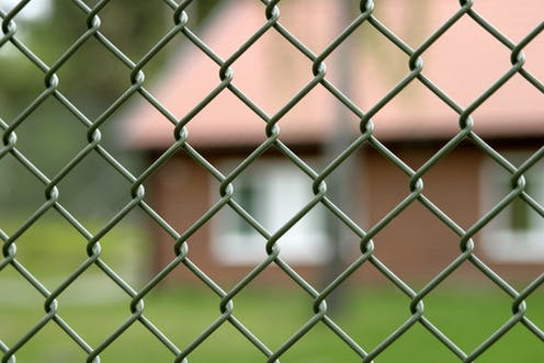Blurred building through chainlink fence