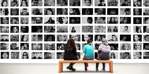 People sitting in front of a montage of faces.