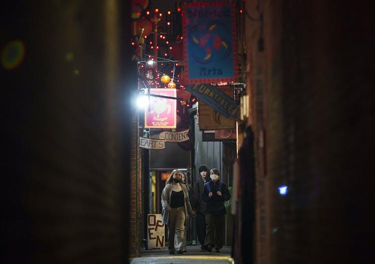 Teens walk in an alley.
