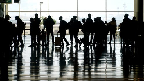 silhouettes of people with bags at an airport