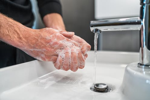 A man washes his hands with soap.