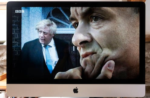 Computer screen BBC TV image of Boris Johnson outside 10 Downing Street door and Dominic Cummings seen in profile.