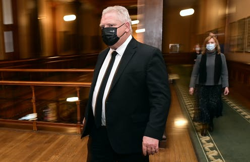 Doug Ford and Christine Elliott, in masks, walk towards the media at Queen's Park.